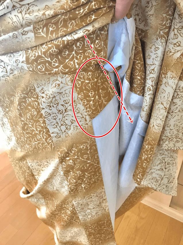 長襦袢の右の衿の先を左側の着物をたくし上げ